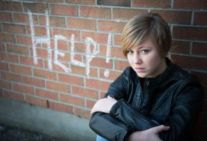Young girl sitting by a wall with the word Help in graffiti on the wall, Rutland Health Network